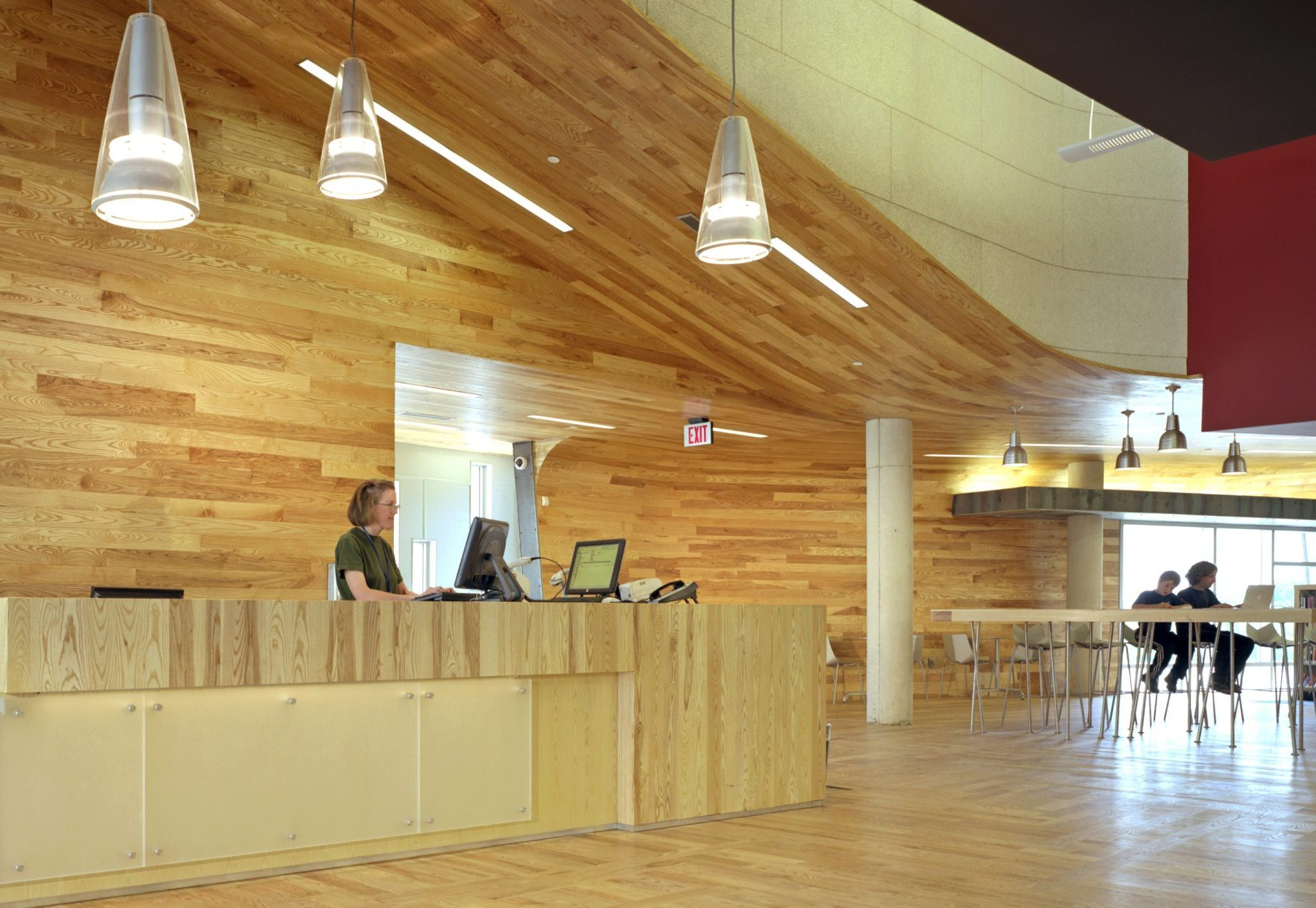 Interior view of ash wood librarian desk at Traverwood Branch of Ann Arbor District Library System Project in Michigan Architecture Interior Design and Sustainable Design