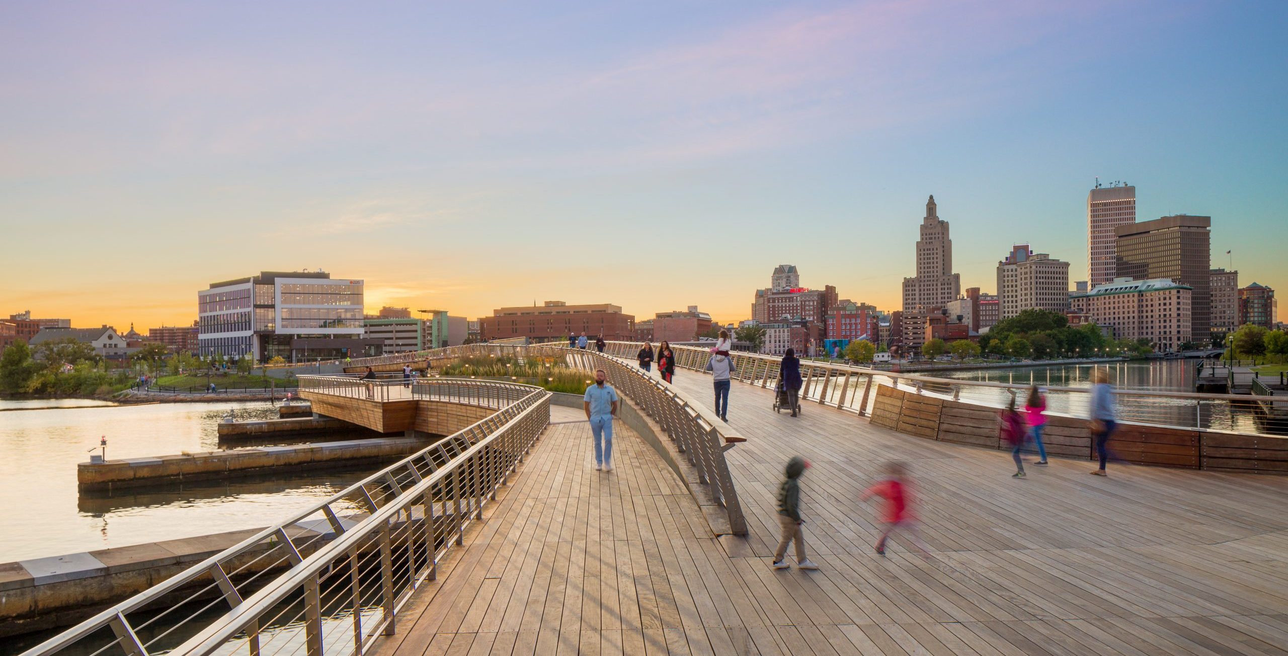 People walking at the entry of Providence River Pedestrian Bridge Project in Rhode Island with downtown skyline in background Urban Design Architecture and Computational Design