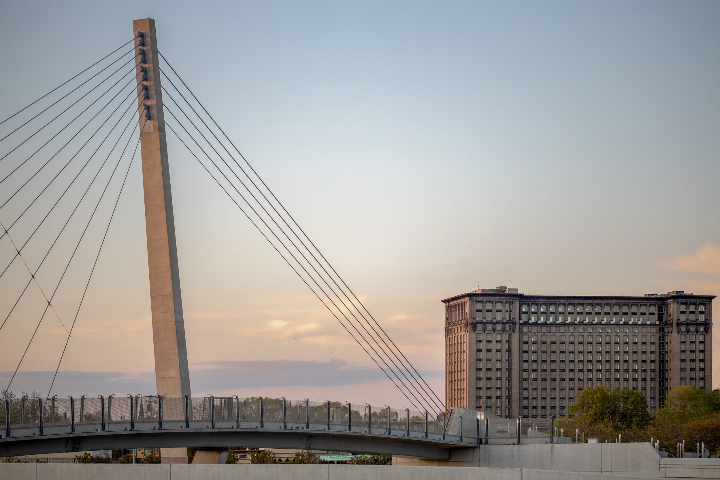 Bagley Avenue Pedestrian Cable Bridge Project with Michigan Central Station in background in Detroit Michigan at sunset Urban Design and Infrastructure