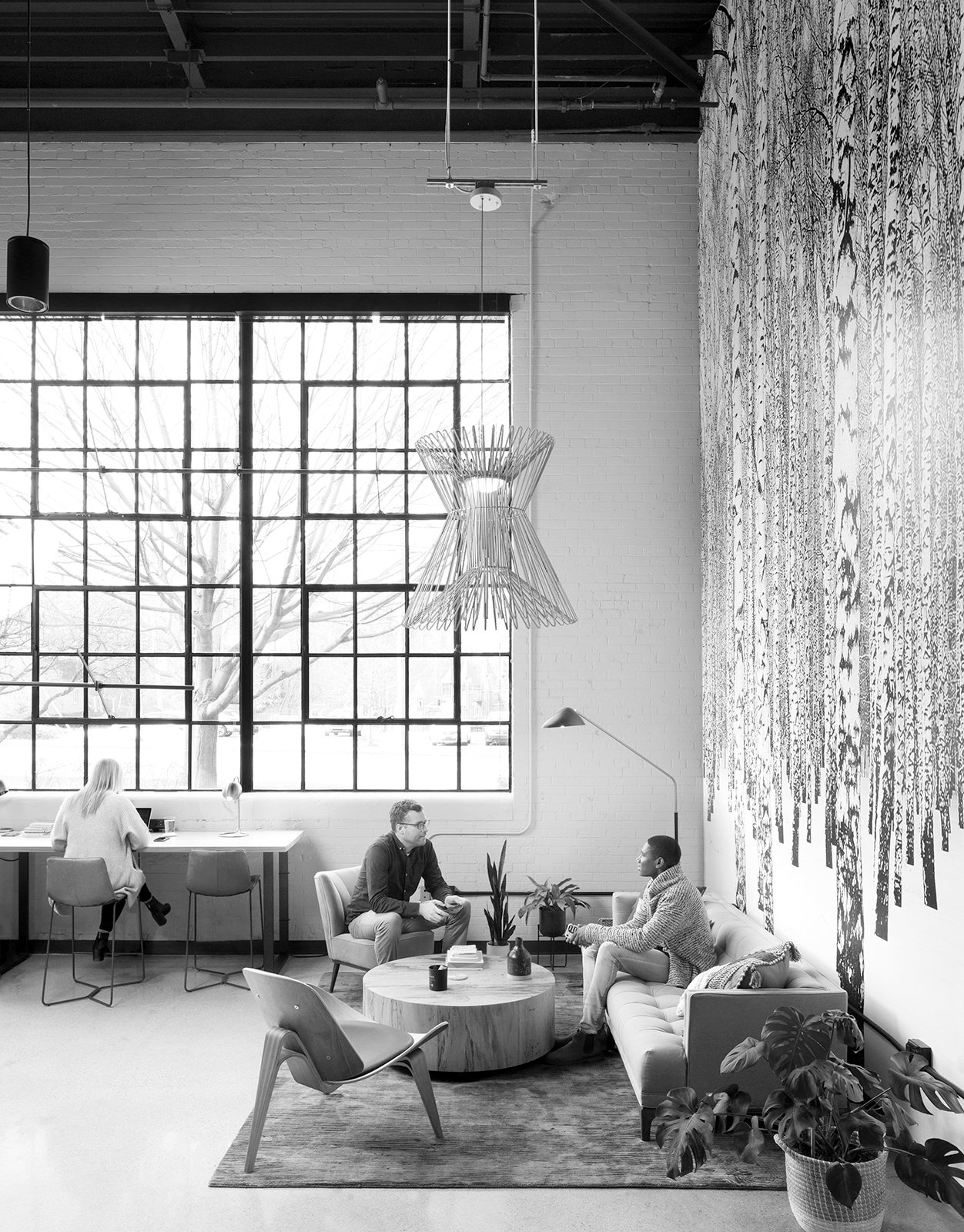 People sitting in AMITY Co-Working lounge project in Northville Michigan Architecture and Interior Design black and white