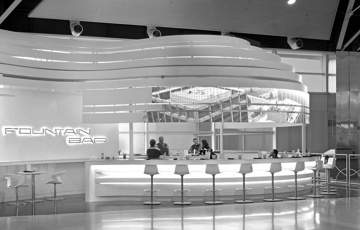 People sitting at illy Caffe and Coffee Bar Project in Detroit Metro Airport McNamara Terminal collaboration with Studio H2G Interior Architecture black and white